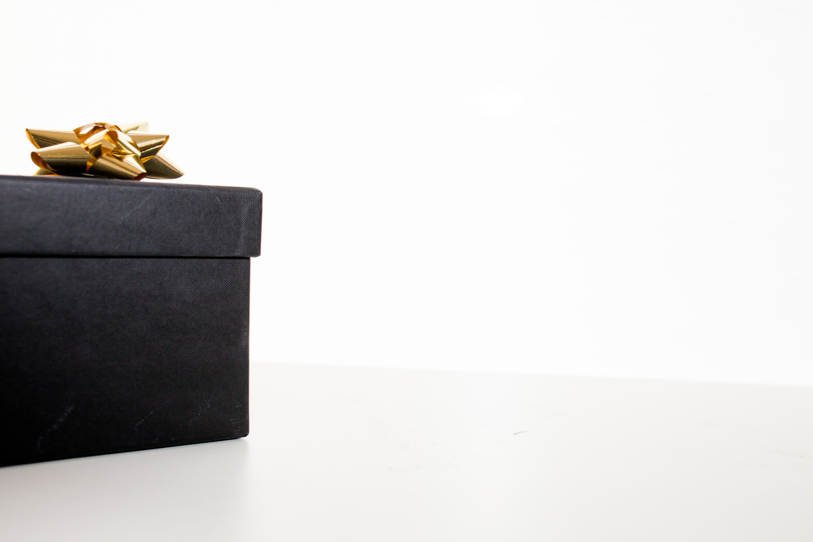Black gift box with golden bow on the left with a plain white background