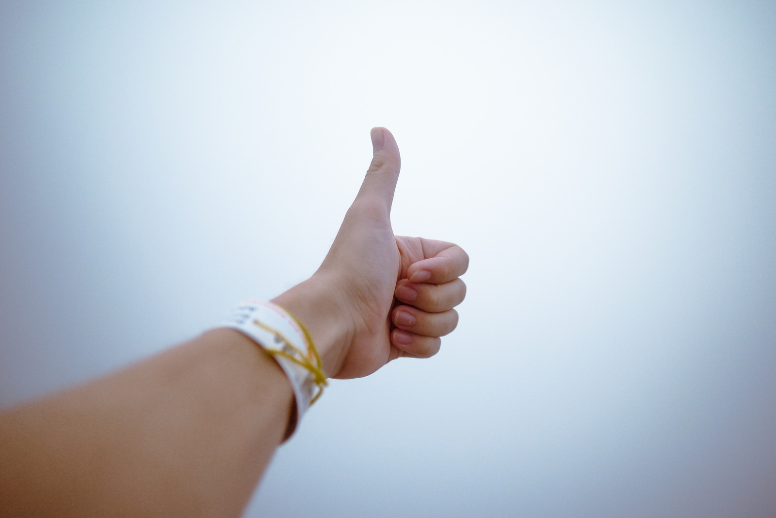 White hand held out in front of body, with a thumb up.